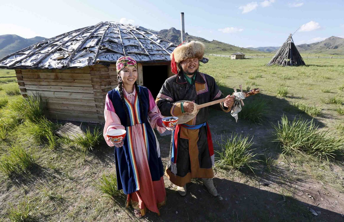 "Members of national folklore and ethnographic groups and employees of a museum-preserve participate in the reconstruction of daily life and traditional holidays celebrated by indigenous population of the Republic of Khakassia during a demonstration for visitors outside a traditional wooden yurt near Kazanovka village, southwest of the city of Abakan, Russia, July 24, 2015. The ""Khakas aal"" (Khakas settlement) ethnographic complex demonstrates the model of a traditional local settlement of the 19th century based on local traditional wooden yurts. The museum preserve is located in a picturesque forest-steppe valley near the Abakan ridge of the Kuznetsk Alatau mountain range and displays numerous objects of the cultural and historical heritage of various epochs accumulated by the people living on this territory, according to representatives. Picture taken July 24, 2015. REUTERS/Ilya Naymushin"