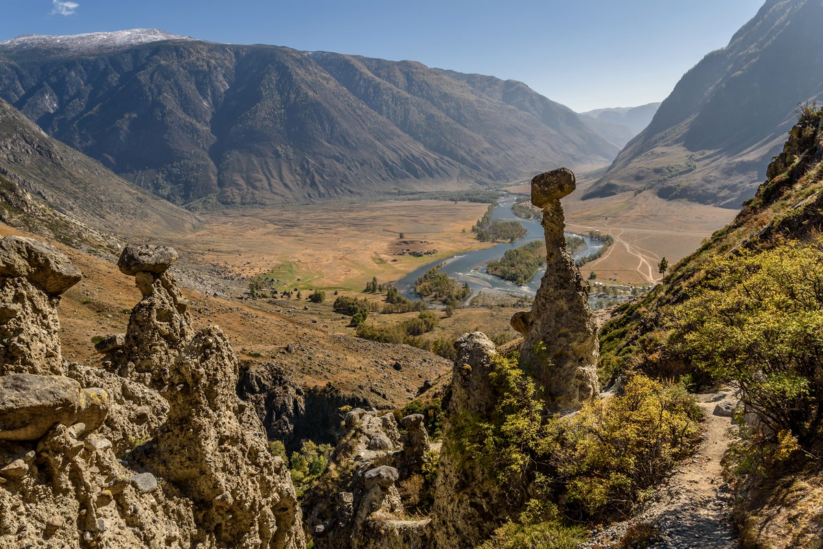 A picturesque autumn top view with high rocks in the form of stone mushrooms on a background of mountains, a valley with a winding river and a blue sky